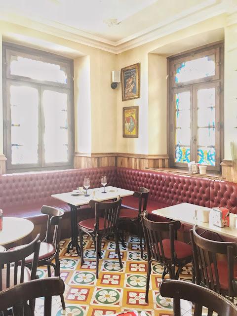 Interior de un bar con suelo de mosaico y grandes ventanales