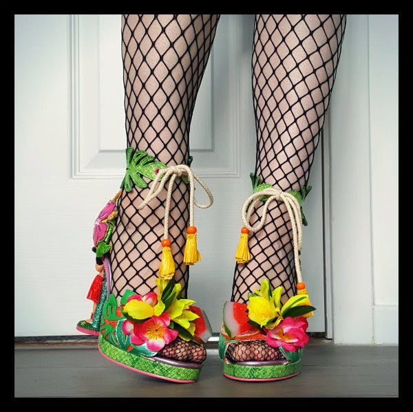 one leg facing one angled wearing fishnet tights and brightly coloured sandals