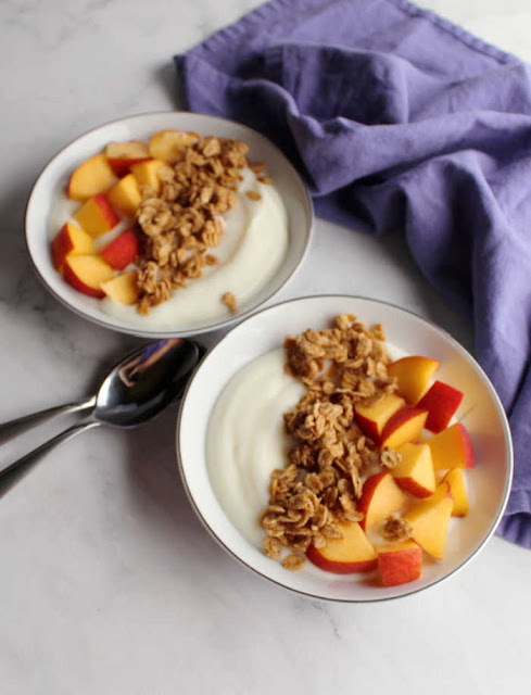 two bowls of yogurt with peach pieces and fresh granola
