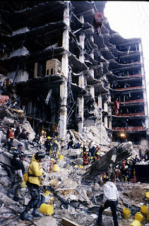 Rescue workers standing in front of building ruins