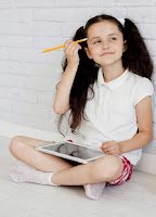 Child sitting down with a tablet and pencil