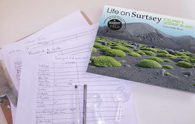 A picture of a children's book title Life on Surtsey, laying on top of a clipboard with papers.