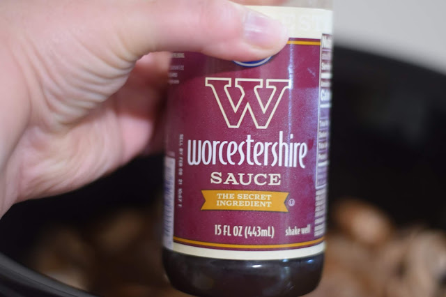 Worcestershire sauce being added to the Salisbury Steaks in the slow cooker.