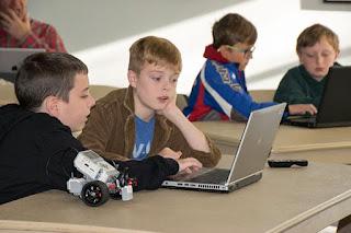 Four boys working on laptops