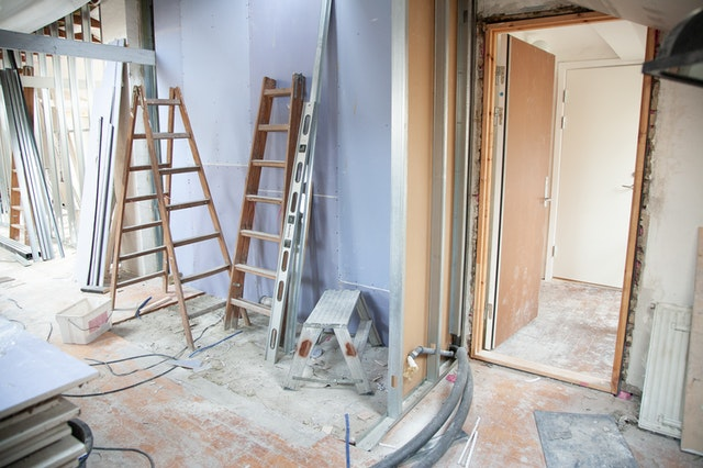 A chaotic room with ladders and equipment due to home renovation