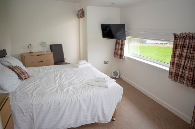 Large bed with cruise like window opposite, tv and dressing table