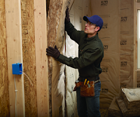 Contractor installing fiberglass insulation