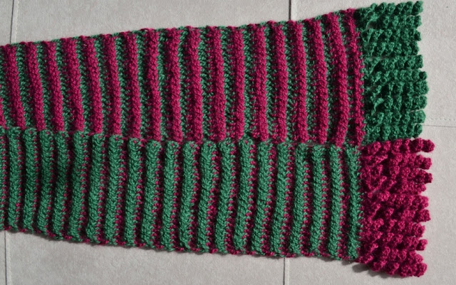 Top view of the bottom half of the scarf showing both the top and reverse sides of the fabric and including the curlicue fringe. The top strip is red (MC) and green and the bottom is green (MC) and red. The fringe on the top half is green and the fringe on the bottom half is red.