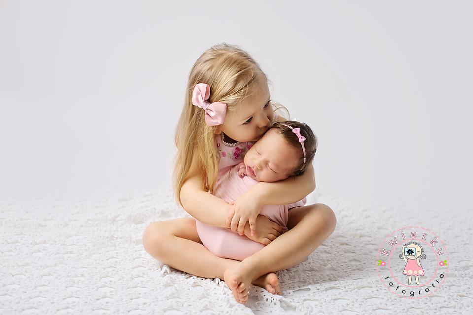 Dziewczynka całuje swoją siostrzyczkę