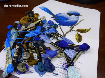 A pile of embroidery floss ready to stitch a blue thread painted bird designed by Trish Burr