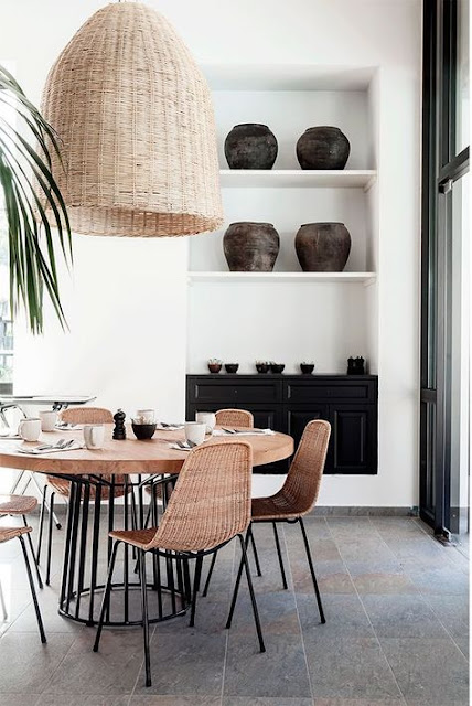 round table with wood top and black metal cage pedestal base and oversized basket lamp hanging above
