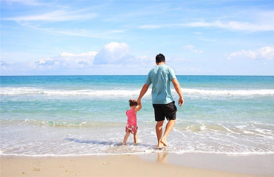 小さな女の子と父親が海で遊んでいる写真