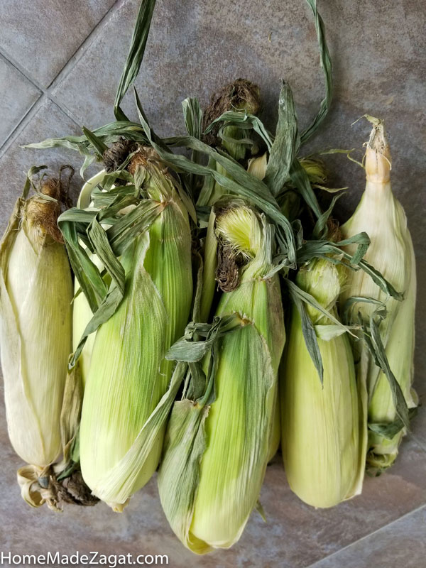 a bussel of corn on the cob in husk