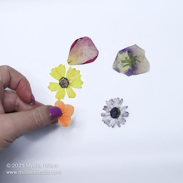 A hand turning flipping the flowers over