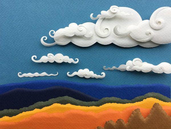 paper sculpture of rolling hills under a partly cloudy sky