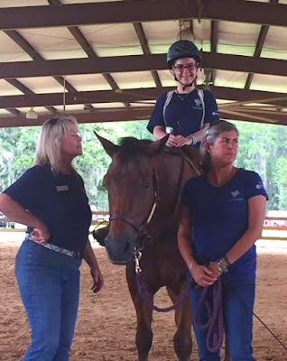Bryanna smiles on the back of a brown horse. Two women are standing on either side of them.