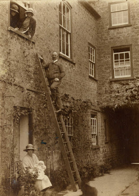 2 ladies leaning out of window, gentleman up ladder. Lady and baby in doorway