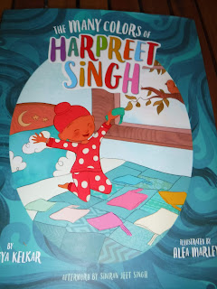 Cover of The Many Colors of Harpeet Singh, shows a picture of a boy with brown skin wearing red pajamas with white polka dots and a red patka, while sitting on a blue bed surrounded by many other colors of patkas