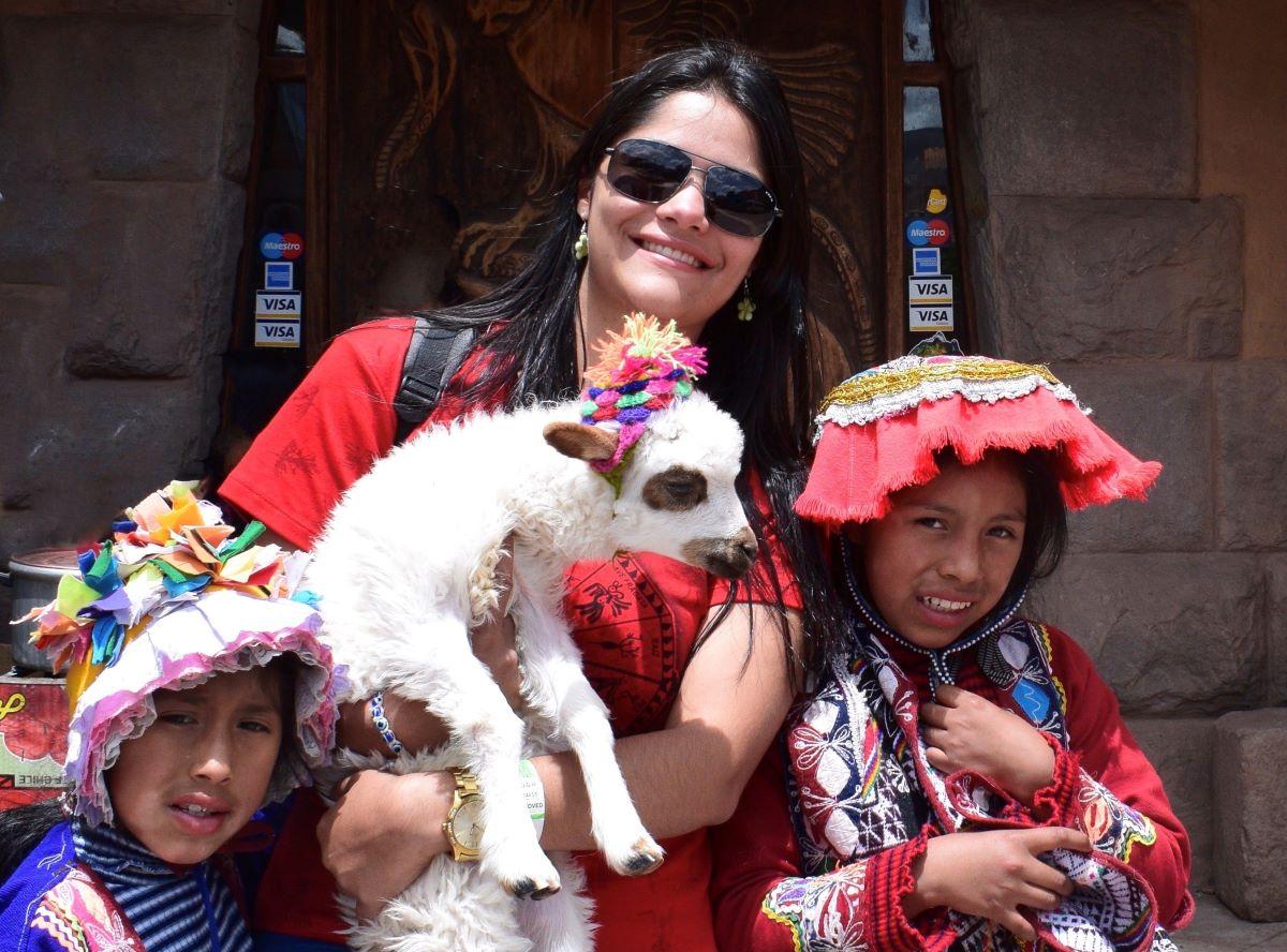 mulher jovem segurando uma alpaca peruna com duas meninas quechuas