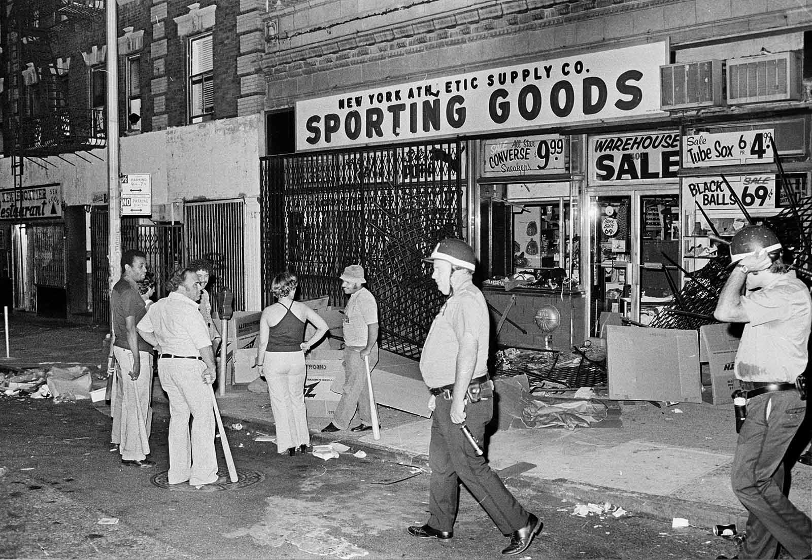 Owners and employees of a sporting goods store stand guard outside with baseball bats after the store on New York City's Upper West Side was looted during massive power failure, Wednesday night, July 13, 1977. Police patrolling the area walk by the store.