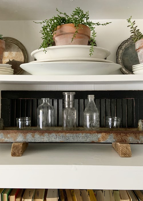 Spring Home Tour - living room white book shelf with black shutters and vintage bottles.