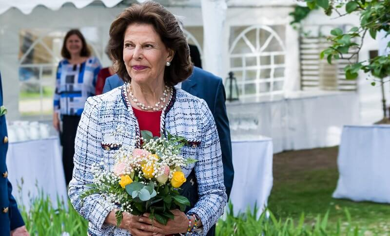 Queen Silvia wore a white tweed jacket and red dress from Chanel, and carried black leather clutch from Chanel