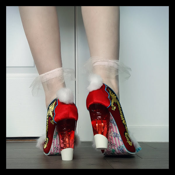 wearing Irregular Choice Ruby Envelope court shoes back with red perspex heel and fluffy pom poms