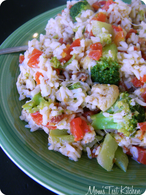 Large green plate full of Chicken, Bacon and Rice Skillet Meal with a serving spoon