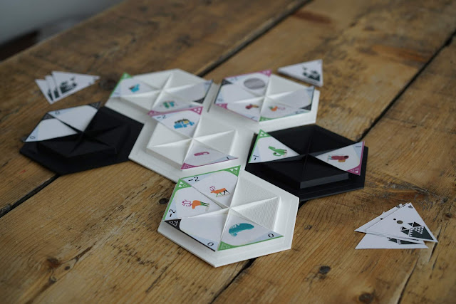 Plastic hexagons with insets where paper triangles with designs on them are placed.