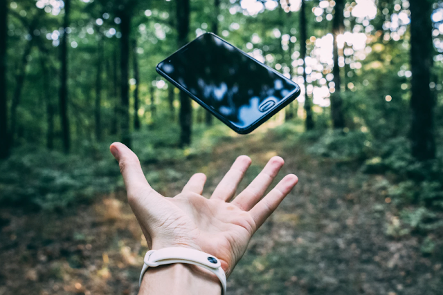 a mobile phone being thrown into the air in the middle of a forest