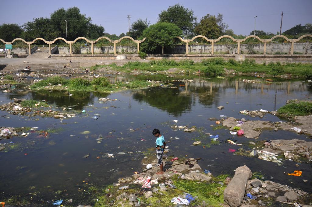Vandforurening er et stort miljøproblem i Indien og den største kilde til vandforurening i Indien er ubehandlet spildevand. Andre forureningskilder inkluderer afstrømning i landbruget og ureguleret mindre industri. De fleste floder, søer og overfladevand i Indien er forurenet på grund af industrier, ubehandlet spildevand og fast affald. Vandforurening er et stort miljøproblem i Indien, som fotografen oplevede på sin gennemrejse i landet. her er en indisk dreng i nærheden af en flod i Nashik, Maharashtra, Indien.