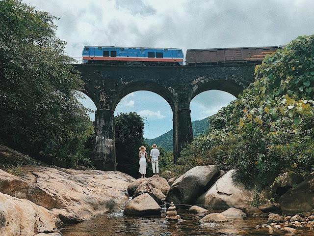 Nằm giáp ranh giữa Đà Nẵng và Huế, khiêm tốn tựa lưng dưới chân đèo Hải Vân, cầu vòm Đồn Cả mang một vẻ đẹp thanh tịnh, tách biệt hẳn với không khí ồn ào, hối hả nơi thành thị. Không giống như những địa điểm du lịch khác, cây cầu cổ kính này được ôm trọn bởi sắc xanh mơn mởn của núi rừng hoang sơ, làm không gian trở nên tĩnh lặng.