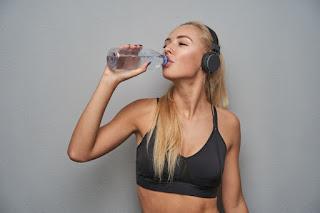 mulher loira fitness bebendo água