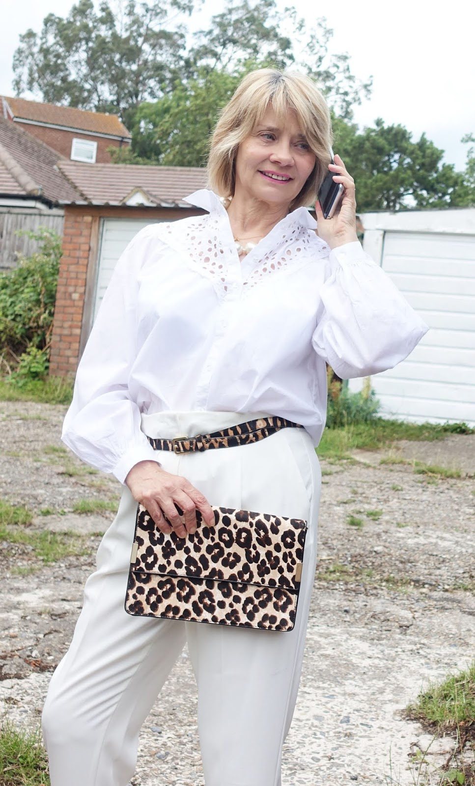 Broderie blouse and white trousers with leopard print accessories worn by over-50s style blogger Gail Hanlon from Is This Mutton