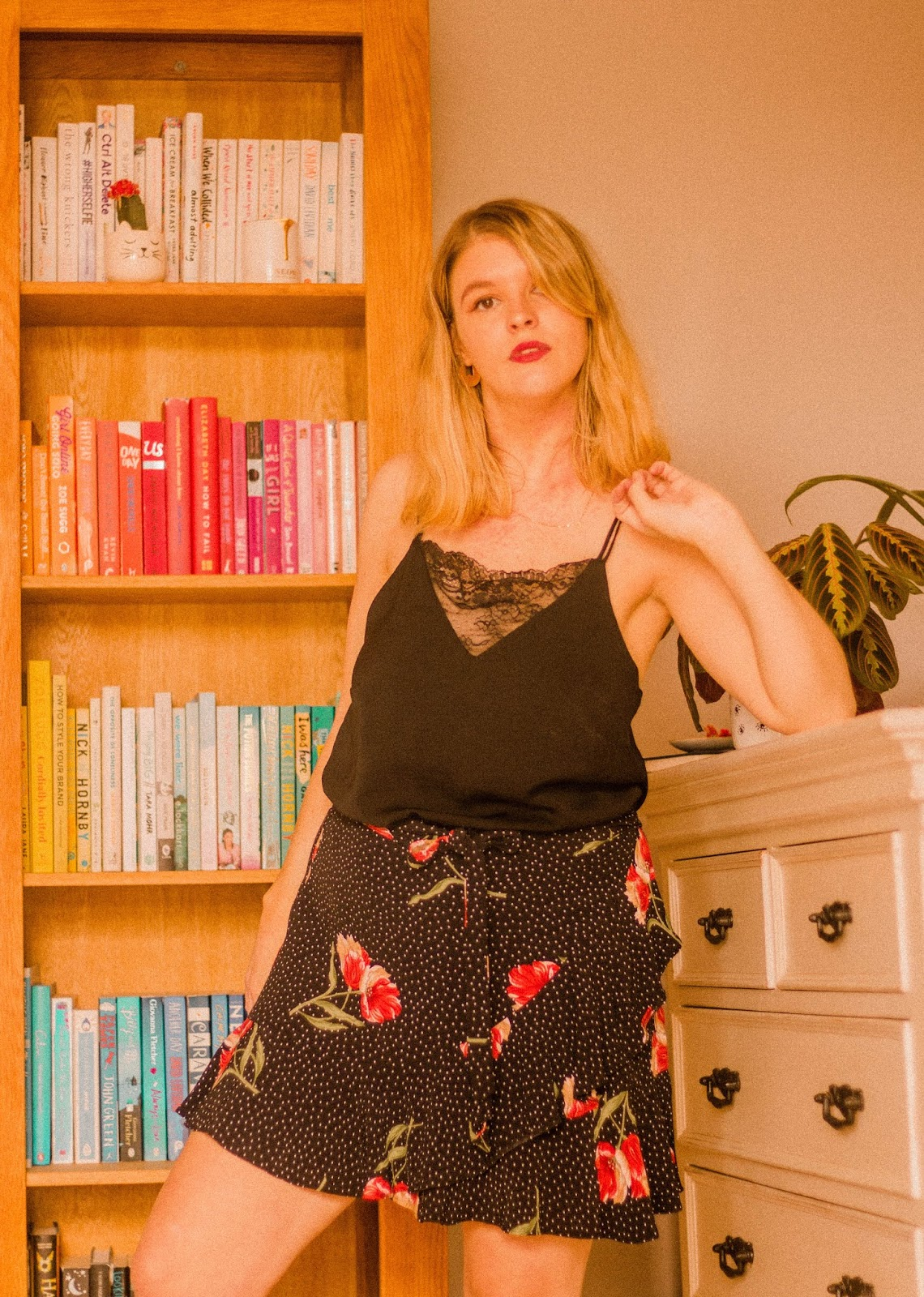 blonde girl with red lip stood in front of book shelf full of colourful books