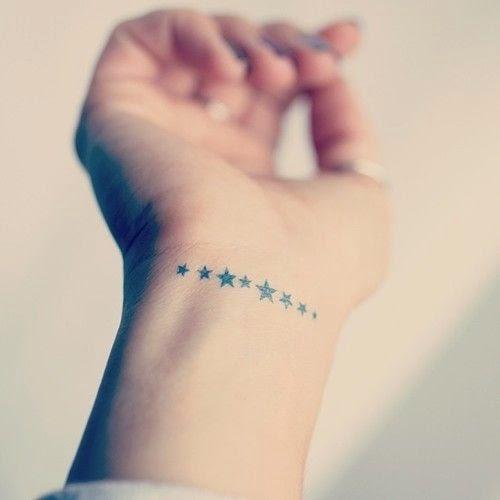 Muñeca de mujer con tatuaje muy elegante de ocho estrellas pequeñas
