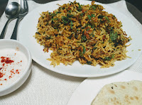 Serving veg biryani with raita and papad