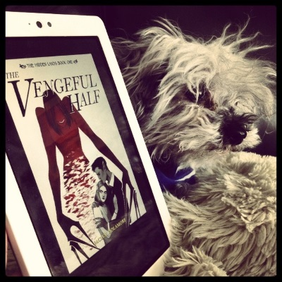 An extremely fuzzy grey poodle, Murchie, peeks out from behind a white Kobo with The Vengeful Half's cover on its screen. The cover features a greyscale image of a pale-skinned girl holding a brown-skinned boy while a red, feminine figure with abnormally long fingers looms over them, ready to snatch them up.