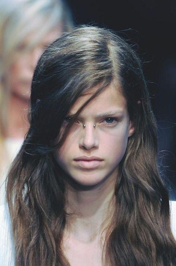 ragazza con bridge piercing capelli lunghi castani e occhi blu