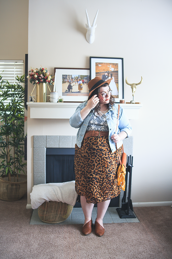 An outfit of a camel brown panama hat, denim jacket, white lace blouse, leopard scarf as skirt and brown d'orsay flats