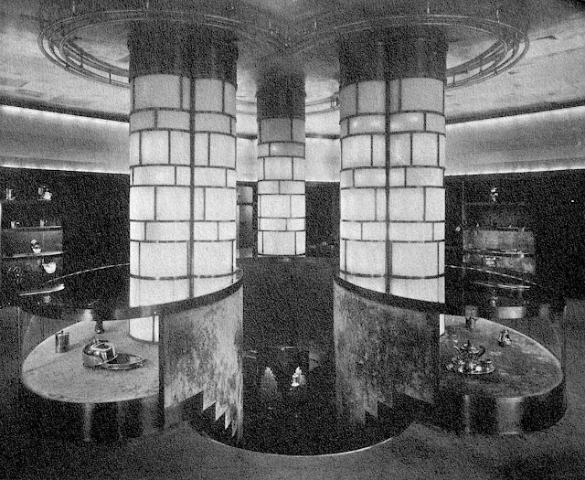 three load bearing illuminated columns above descending stairs in a 1933 store