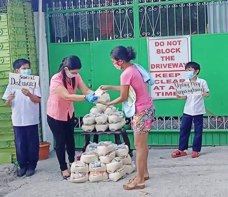 Teacher Jennifer Salcedo hands out relief goods