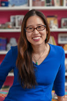 Grace Lin, wearing a blue top and standing in front of the bookshelves in her home office.