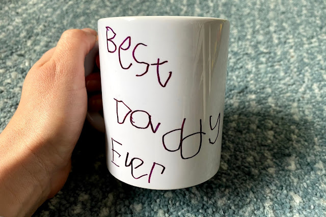 """A hand holding a white mug with a handwritten message saying """"Best Daddy ever"""""""