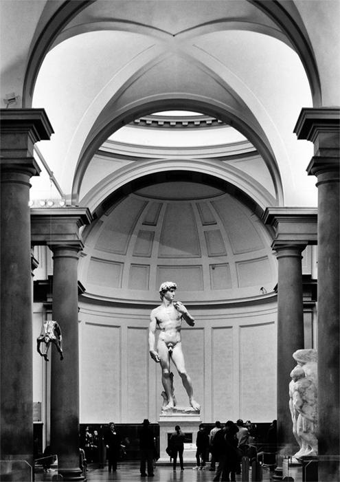 Imagen en blanco y negro de El David de Miguel Ángel Buonarroti original en el Museo de la Galería de la Academia de Florencia, al fondo, en donde se aprecian haciendo de pasillo algunos de los esclavos inacabados que debían decorar la Tumba del papa Julio II del mismo artista