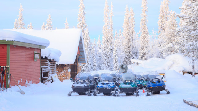 a group of snowmobiles outside the lodge waiting for riders