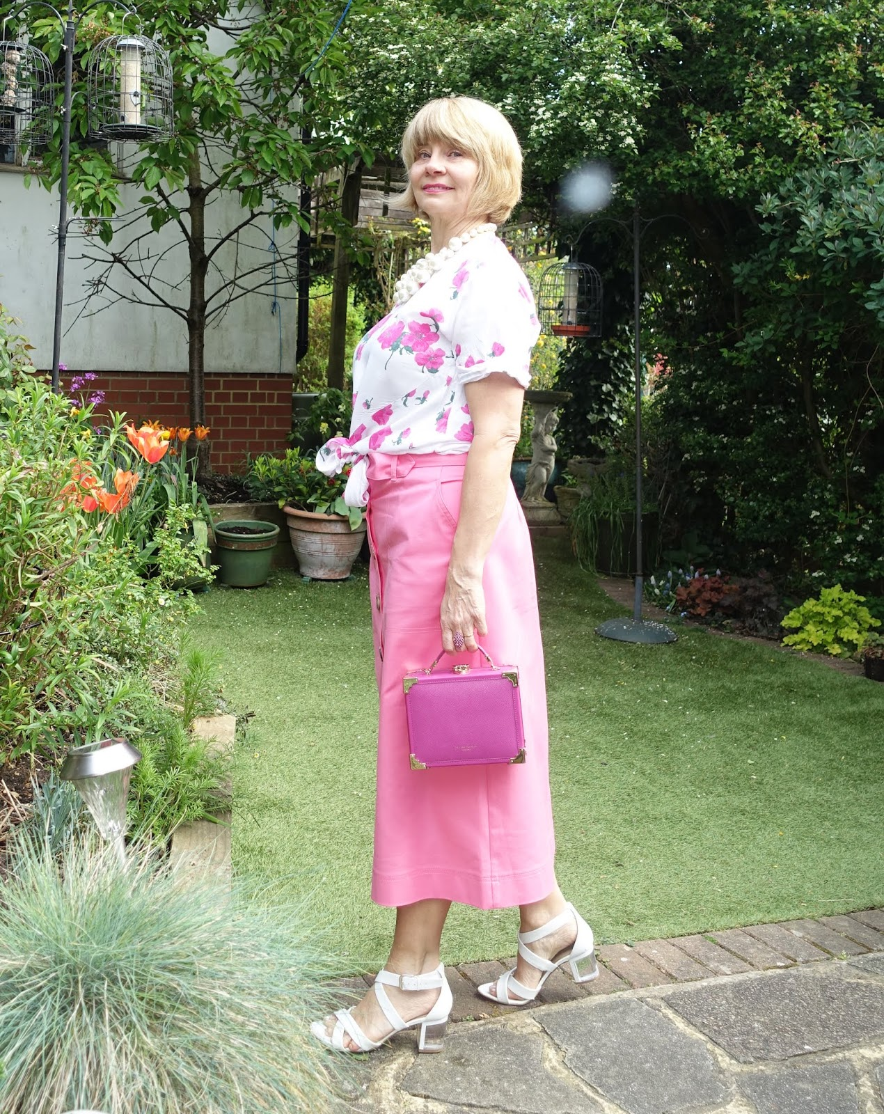 Pink midi skirt from Marks and Spencer worn with pink and white rose print blouse and white 40s style wedges.