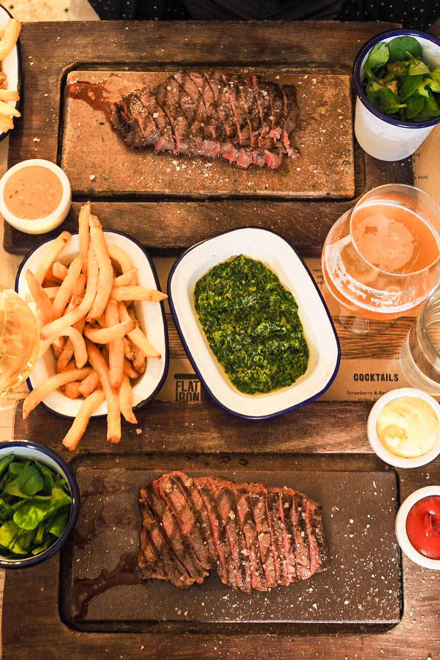 Two flat iron steaks with chips, creamed spinach and beer