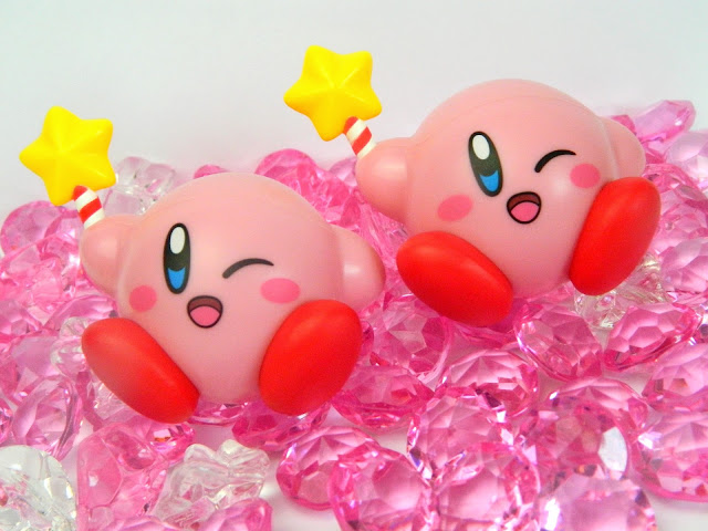 Two Nintendo Kirby figures holding star-wands and sitting on plastic gems