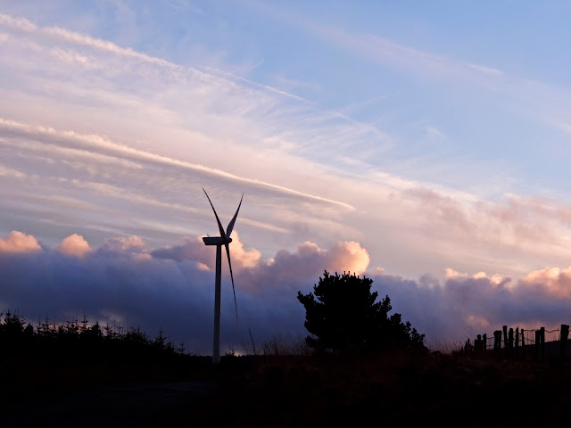 Landscape photo of a windmill at sunset with clouds.
